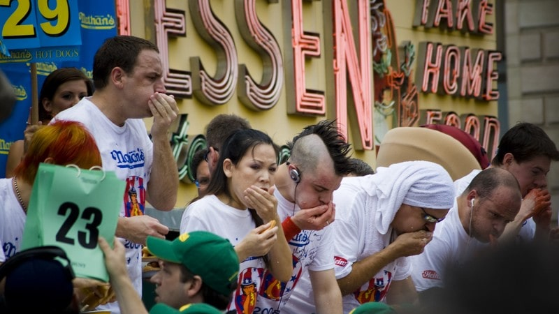 Competitive eaters eat at Coney Island in the Nathan's Famous hot dog eating contest every Fourth of July