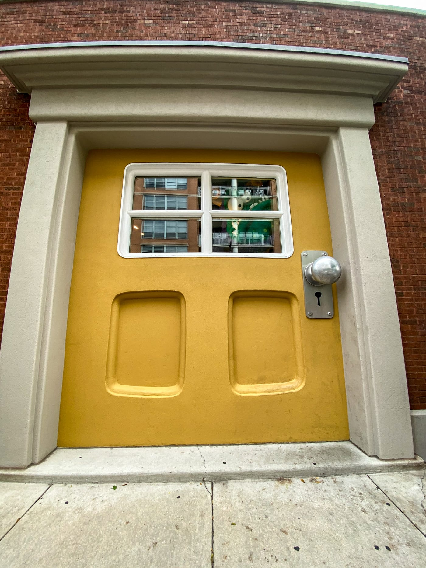 Big Monster Door at Big Monster Toys in Chicago, Illinois   A giant yellow door with a monster peeking out the window in the West Loop