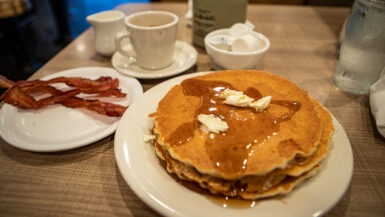 Pancakes with butter and maple syrup and a side of bacon at Lou Mitchell's Restaurant on Route 66 in Chicago, Illinois