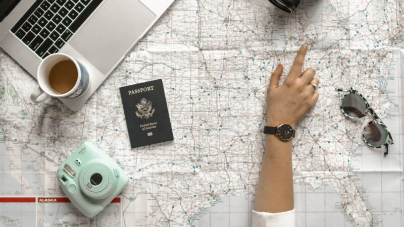 How to plan a road trip with Google Maps - woman pointing at a road map with a camera, passport, and laptop